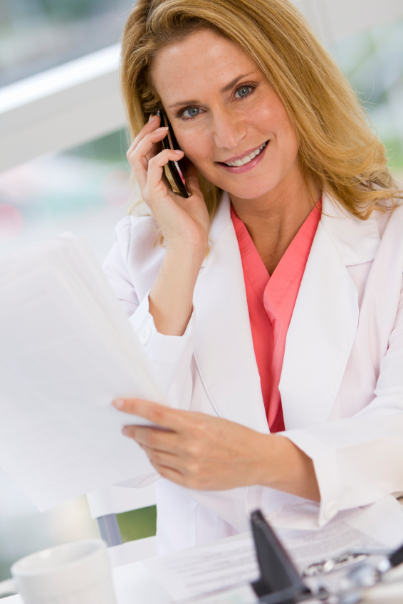Caucasian female wearing lab coat and holding cellphone